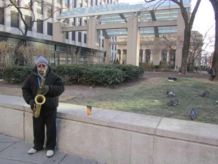 This guy is actually playing to a group of people braving the cold for a smoke break, but I liked the shot with the pigeons most.