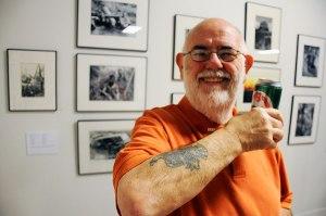 Man in orange shirt shows off tattoo